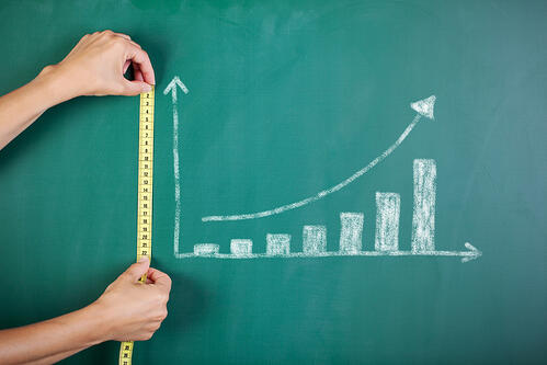 Closeup of womans hands measuring bar graph with tape on blackboard